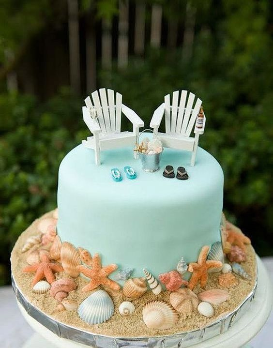 a beach tiffany blue wedding cake with loungers, flipflops, a bucket with seashells and seashells and sand around