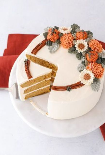a beautiful pumpkin spice wedding cake covered with white buttercream, with bright sugar blooms and pumpkins, with sugar leaves