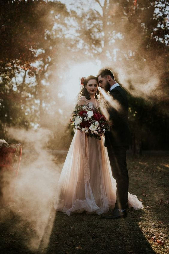 a beautiful winter wedding portrait with smoke and some sunshine going through the smoke is wow