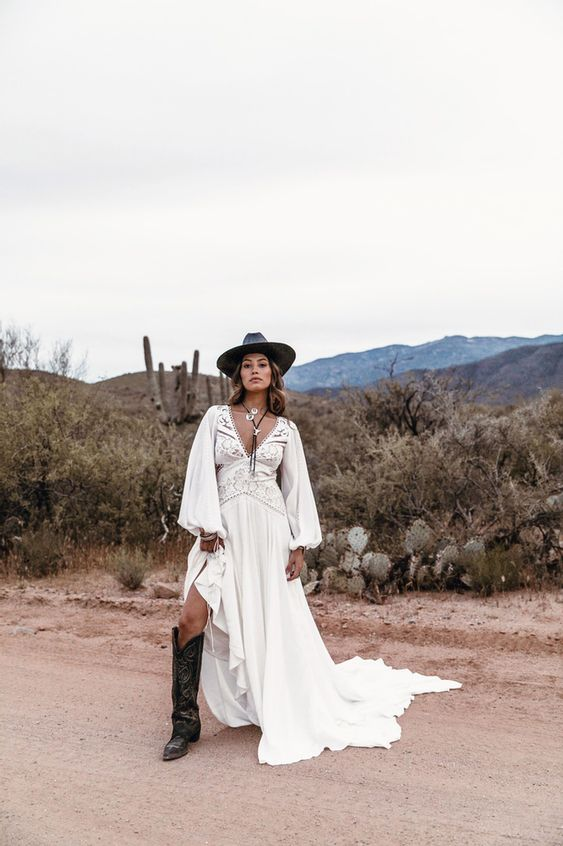 a boho bridal outfit with a gorgeous boho lace wedding dress with a train, a black hat, tall black cowgirl boots and statement accessories