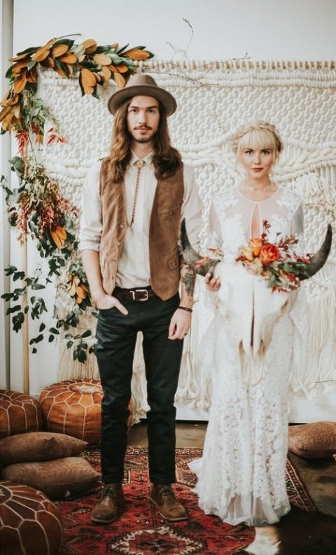 a boho groom's look with a white shirt, a bolo tie, a brown leather vest, black jeans, brown shoes and a camel hat