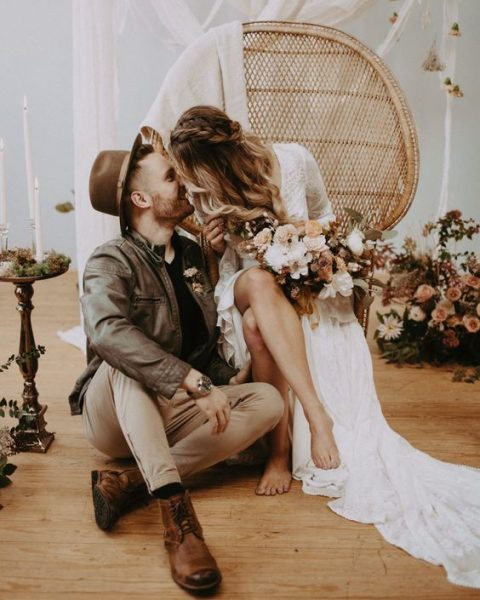 a boho groom's outfit in earthy tones with tan pants, brown shoes, a black shirt and a brown leather jacket plus a brown hat
