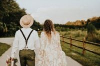 a boho groom's outfit with green pants, brown boots, a white shirt, suspenders and a neutral hat