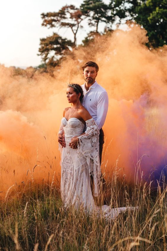 a boho wedding portrait in the field with colorful smoke all around – it highlights the space