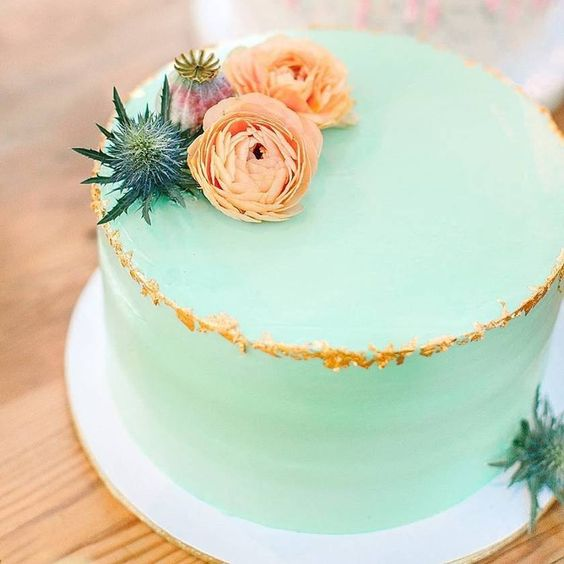 a bold mint green wedding cake with gold leaf and coral blooms and a thistle on top