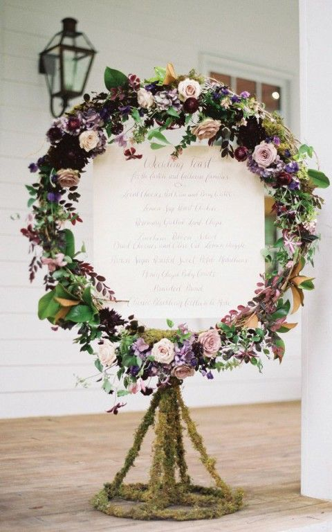 a bright and cool fall wedding wreath of blush, deep purple, lilac and white blooms, greenery and dark foliage and a wedding toast inside