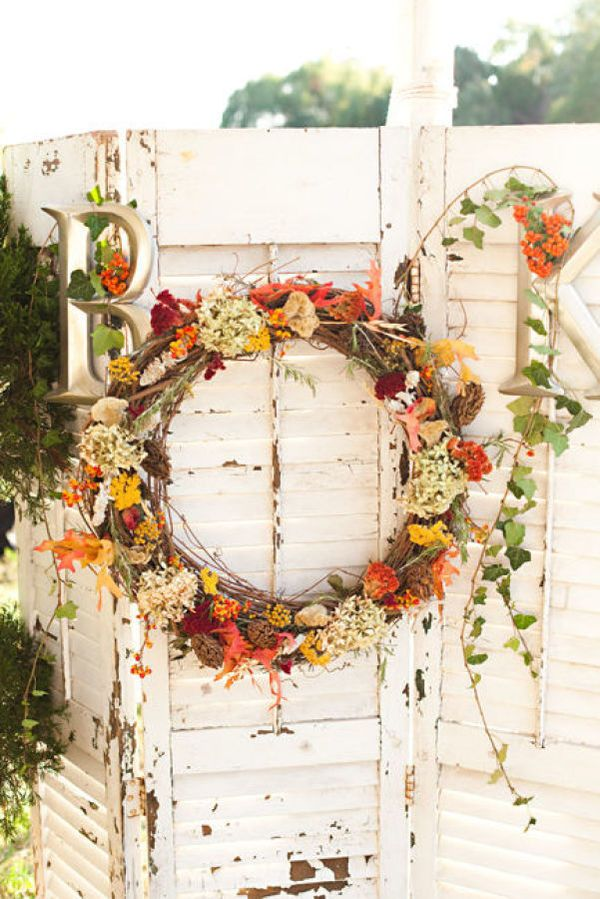 a bright fall wedding wreath of vine, white, burgundy and orange blooms and leaves and some monograms for rustic fall decor