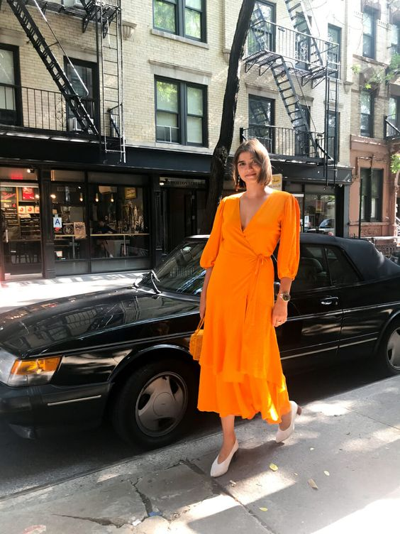a bright orange midi wrap dress with long sleeves, trendy white shoes and a small bag