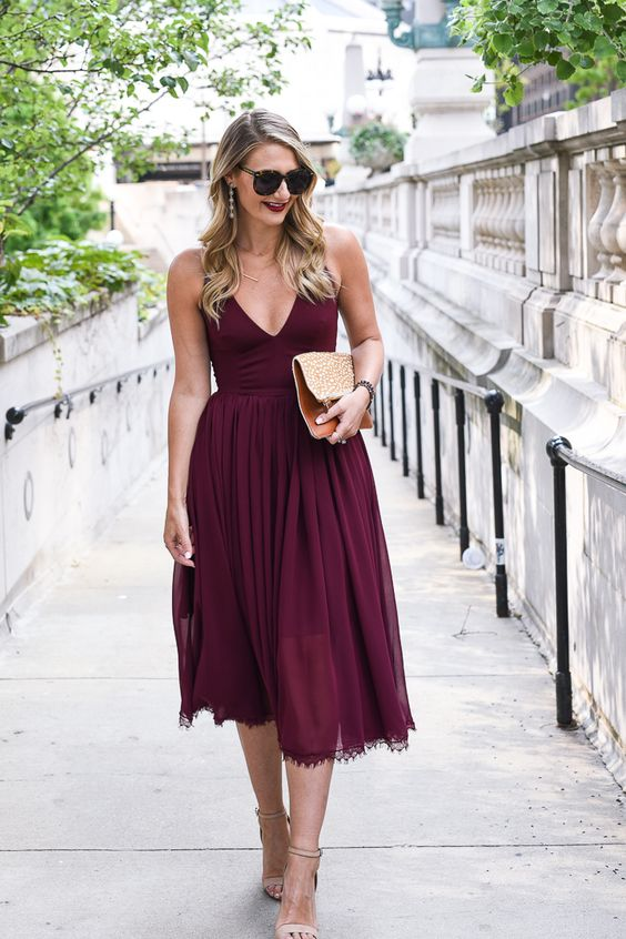 a burgundy strap midi dress with a deep V-neckline, a lace trim, nude heels and an embellished clutch