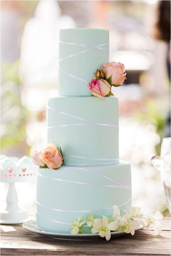 a chic mint green wedding cake with shiny ribbon, fresh pink and neutral blooms looks very bold