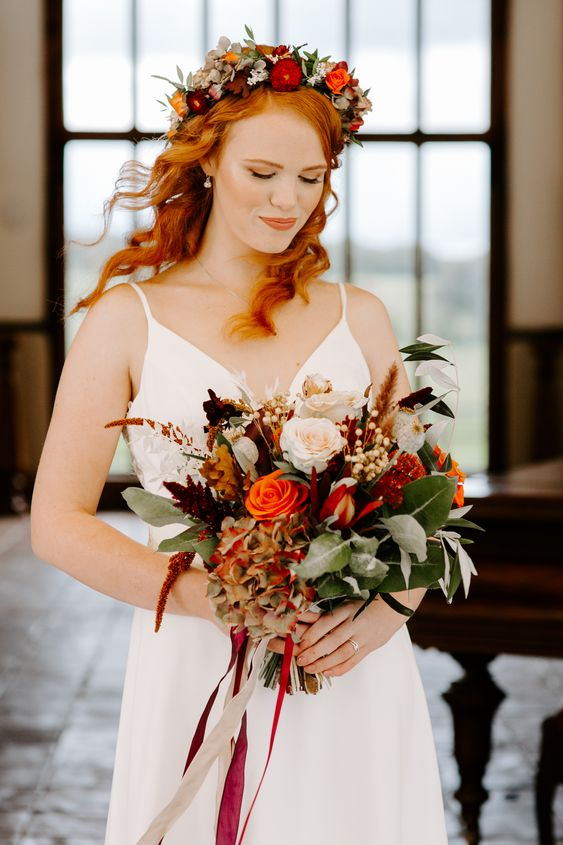 a colorful fall bridal crown with deep red, burgudy and orange blooms, foliage and greenery is a lovely idea