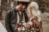 a cool boho groom's outfit with brown pants, a printed shirt, a neutral waistcoat, a black leather jacket and a white hat
