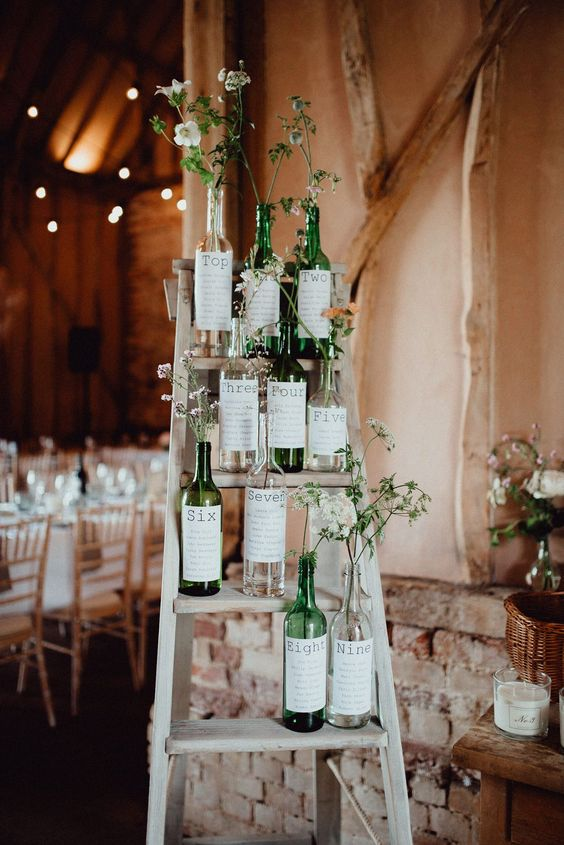 a creative wedding chart of wine bottles with stickers and greenery and wildflowers for a vineyard wedding