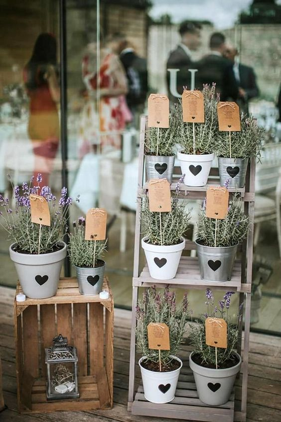 a creative wedding seating chart of a ladder, blooms in pots and seating plans tucked into the pots