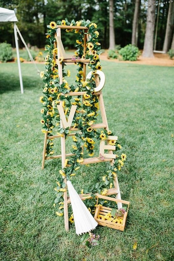 a cute rustic wedding decoration of a ladder, greenery, sunflowers and wooden letters is a cool idea