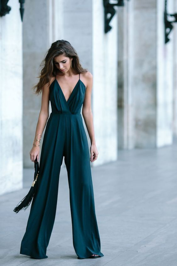 a dark green jumpsuit on spaghetti straps, with wideleg pants and a tassel clutch