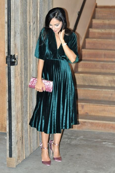 a dark green velvet midi dress with long sleeves, a pleated skirt, a deep V-neckline, pink shoes and a pink clutch