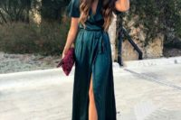 a dark green wrap midi dress with short sleeves, a floral clutch and nude shoes for a fall wedding