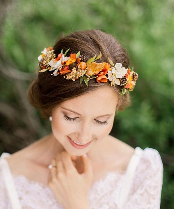 a delicate and bright fall wedding crown of orange and rust bloo,s white blooms, pinecones and berries is a very pretty idea