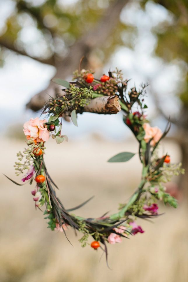 a delicate fall wedding wreath of greenery, blush and fuchsia blooms and berries is a pretty decoration for the fall
