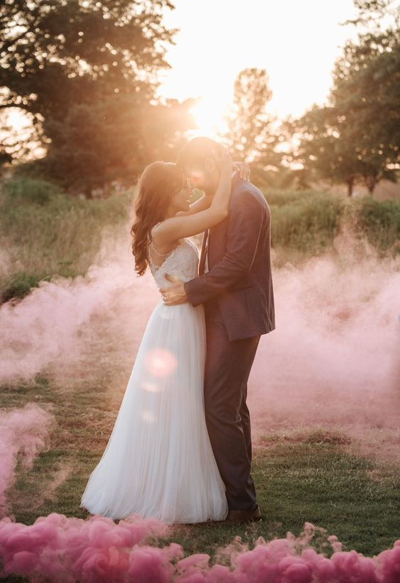 a delicate wedding portrait done with sunshine and pink smoke around looks gorgeous and ethereal