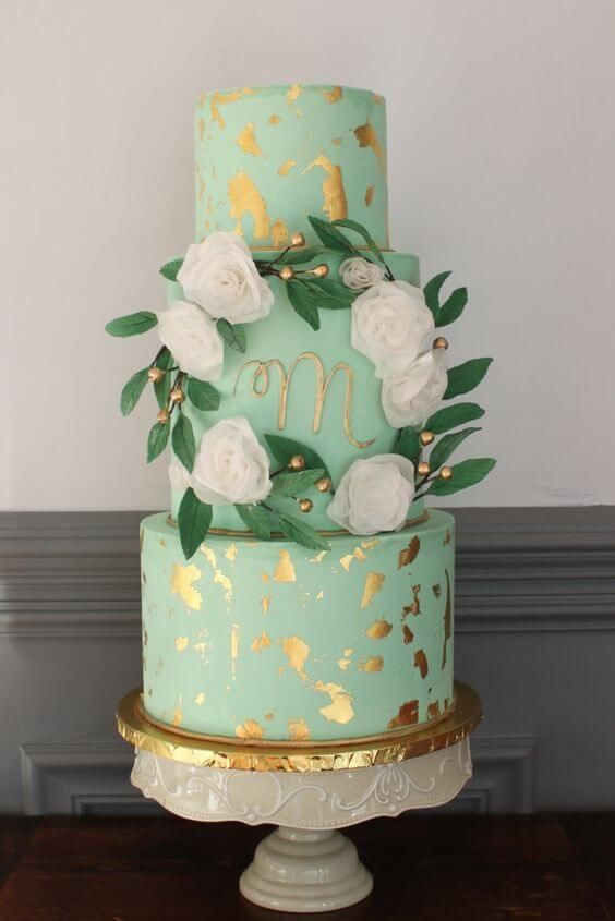 a glam mint and gold flake wedding cake with a monogram, fake blooms and foliage on a chic stand