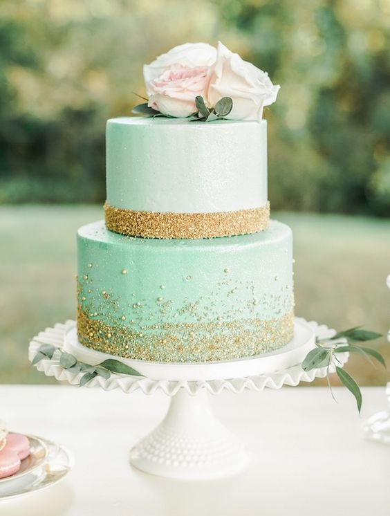 a glam mint wedding cake with gold glitter and beads and some fresh roses on top