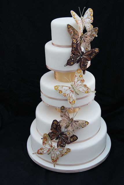 a gorgeous wedding cake in white, with tan ribbons, gold touches and beautiful and refined butterflies for decor