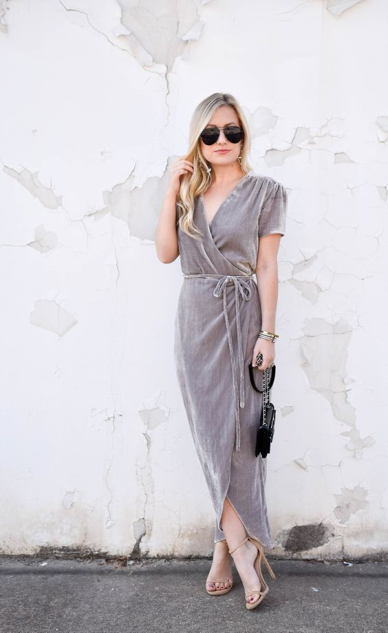 a grey wrap velvet dress with long ties, short sleeves, nude heels and a small black bag