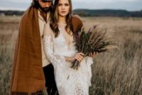 a groom wearing a hat and a brown cover up instead of a jacket for a relaxed and informal boho look