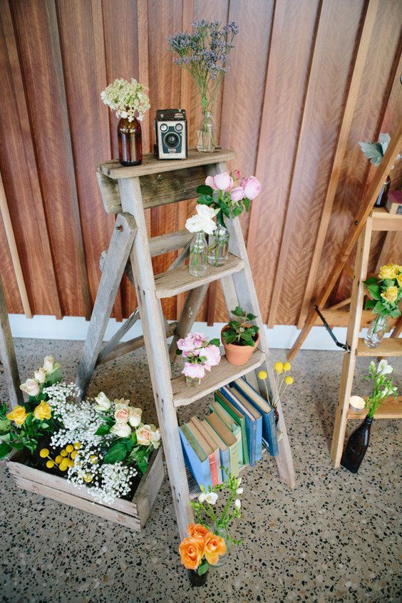 a ladder with potted blooms, books, cameras and bottles is a chic and cool decoration for a rustic wedding