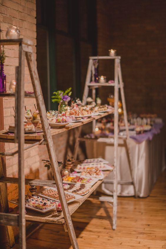 a large dessert station of two ladders and wooden planks, with greenery and blooms and lots of sweets