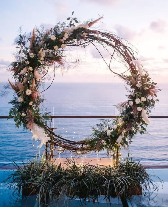 a large fall wedding wreath covered with white blooms, leaves, pampas grass and twigs plus LED lights is a very cool idea