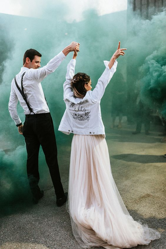 a lovely wedding photo with the couple wearing black and white and green smoke around accenting them and making them stand out