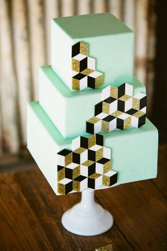 a mint green wedding cake decorated with white, black and gold glitter cubes for decor