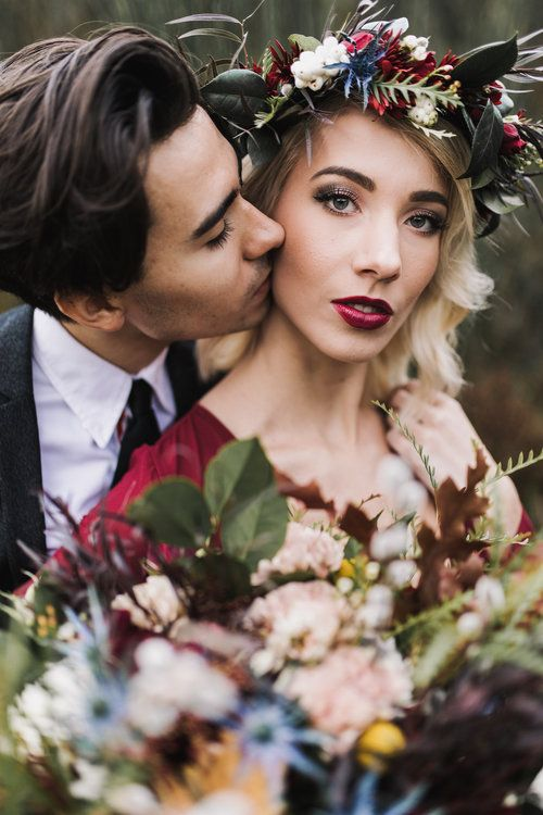 a moody floral crown with deep red, berries, greenery and dark foliage is a lovely idea for a fall boho bride