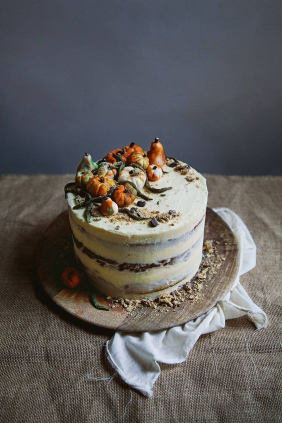 a naked wedding cake topped with sugar pumpkins and leaves is a lovely idea for a fall wedding