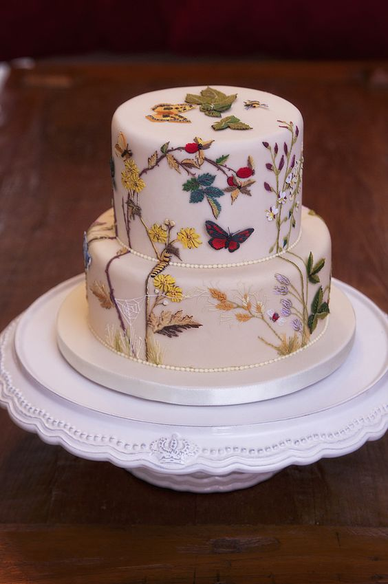 a painted wedding cake with flowers, laves, branches and butterflies is a lovely and bold idea to go for, looks amazing