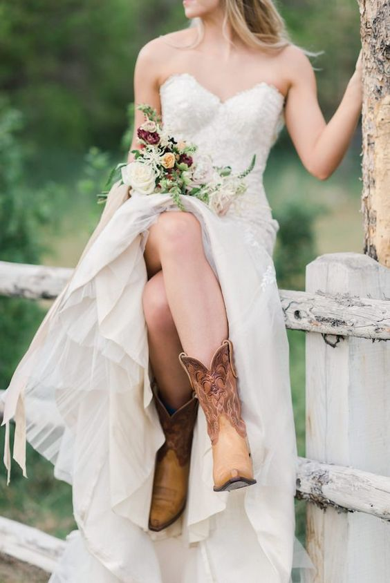 a pretty glam strapless wedding dress with an embellished bodice, a tulle skirt, brown cowgirl boots with patterns for a fall wedding