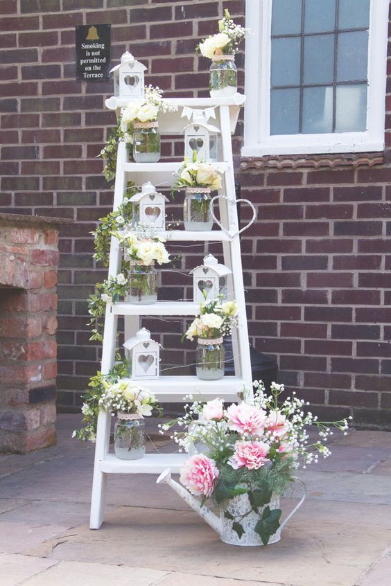 a pretty rustic wedding decoration of a white ladder, white blooms and greenery, white candle houses