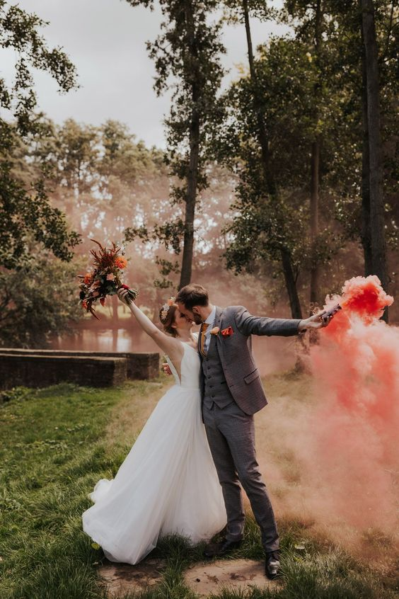 a pretty wedding portrait done with a red smoke bomb that echoes with the blooms in the wedding bouquet and accents the couple
