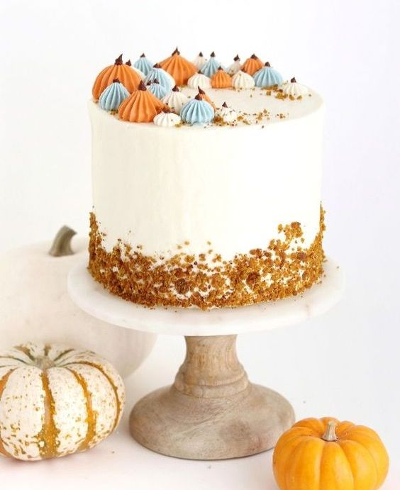 a pumpkin spice wedding cake with cream cheese buttercream, with colorful pumpkin-inspired meringues, with rust crusts