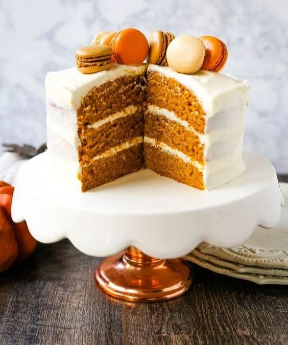 a pumpkin spice wedding cake with cream cheese frosting and macarons on top is a lovely idea for a modern fall wedding