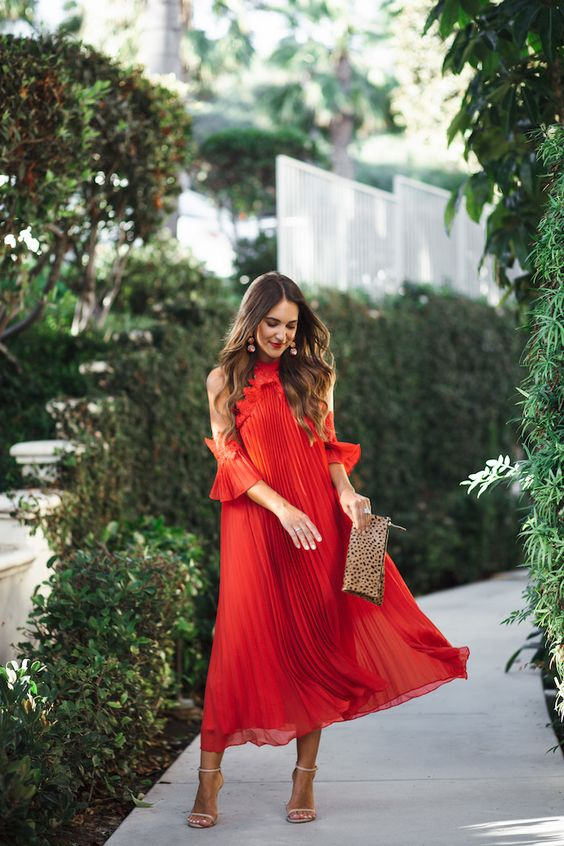 a red pleated midi dress with open shoulders, nude shoes and a printed clutch plus statement earrings