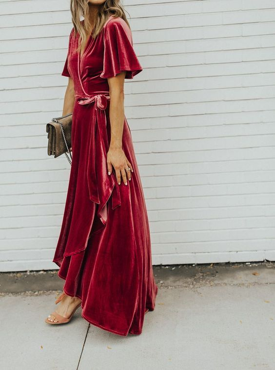 a red velvet wrap maxi dress with short sleeves, tan shoes and a matching small bag