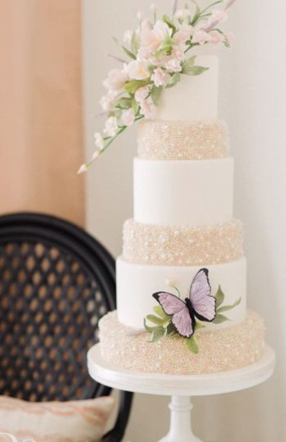 a refined wedding cake with white and neutral pearl tiers, with sugar blooms and leaves and a purple butterfly is gorgeous
