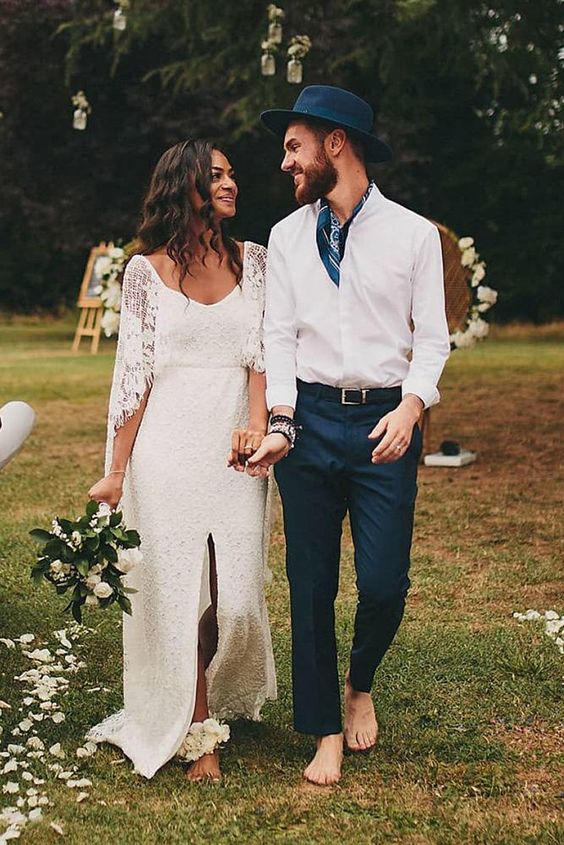 a relaxed and bold groom's outfit with navy pants, a printed navy tie and hat plus a white shirt