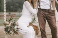 a relaxed boho groom's look with brown pants and shoes with no socks, brown suspenders and a black hat