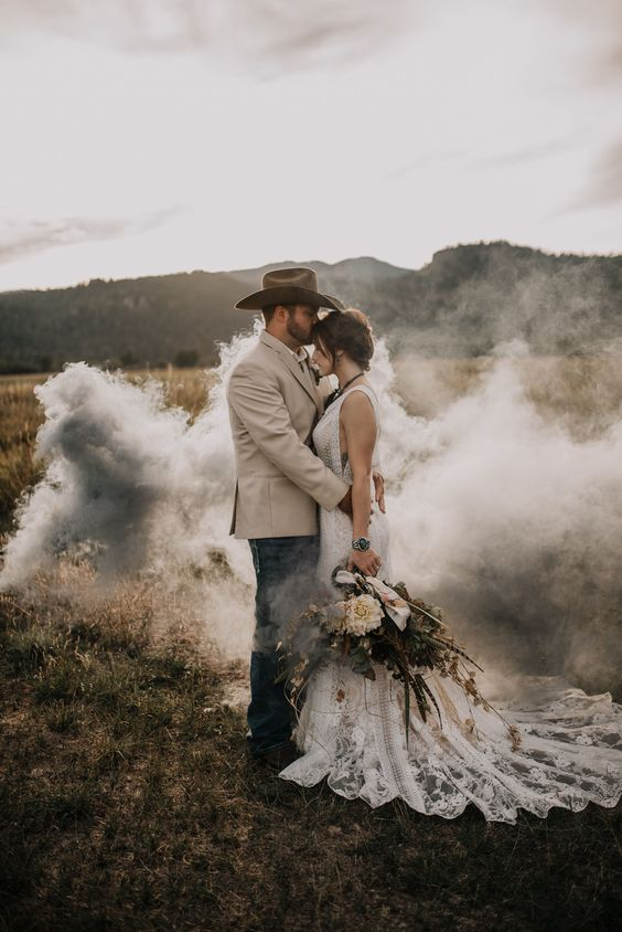 a romantic boho wedding portrait in the field made very special and eye-catchy with a grey smoke bomb