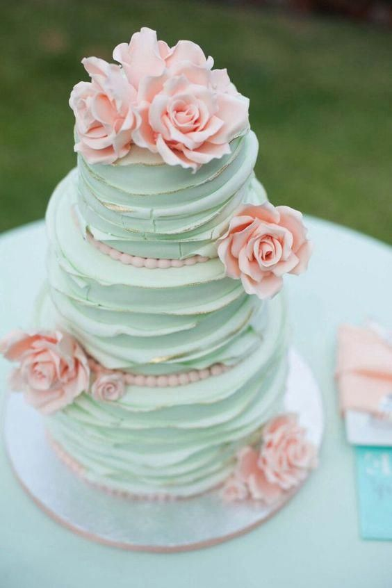 a romantic mint green wedding cake decorated with pink beads and pink sugar blooms